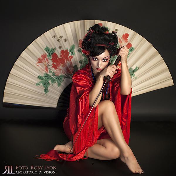 donna con veste orientale, ventaglio e katana